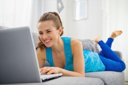 divan: Mujer joven feliz puesta en sof� y utilizando equipo port�til