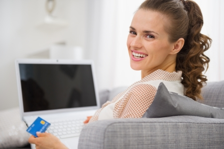 smiling young housewife with laptop and credit card sitting on