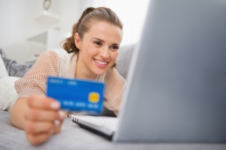 Happy young woman laying on divan with laptop and credit card Stock Photo - 19982999
