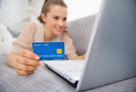 Closeup on credit card in hand of young woman laying on couch Stock Photo - 19983030