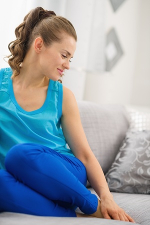 Happy young woman sitting on sofa in living room Stock Photo - 19982997