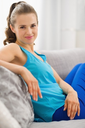 Happy young woman sitting on couch in living room Stock Photo - 19982998