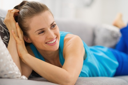 Happy young woman laying on couch in living room and looking on copy space