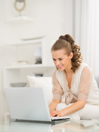 divan: Happy young housewife sitting on divan and using laptop Stock Photo