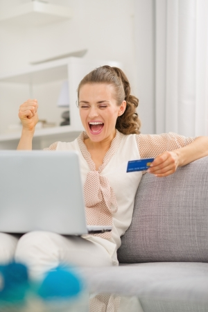 rejoicing: Happy young housewife with laptop and credit card rejoicing success Stock Photo