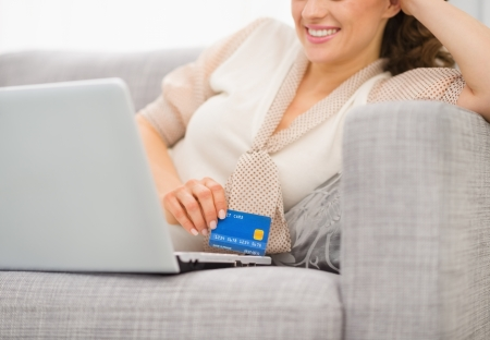 Closeup on credit card in hand of smiling woman with laptop Stock Photo - 19983033