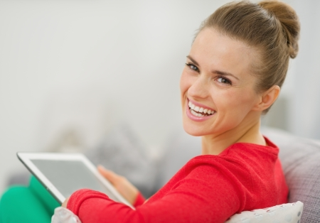 topicality: Smiling young woman sitting on couch and using tablet pc Stock Photo