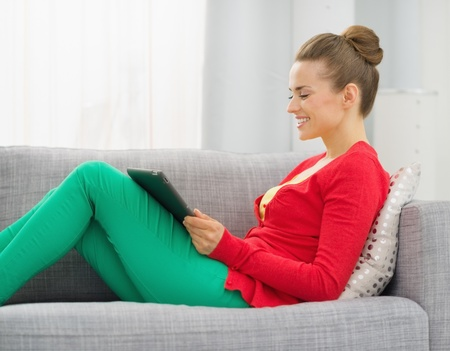 Smiling young woman sitting on divan and using tablet pc Stock Photo - 19983046