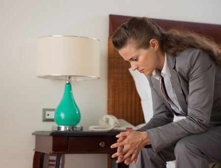 Stressed business woman sitting on bed in hotel room Stock Photo - 20309989