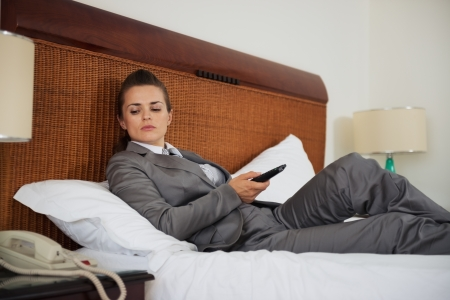 disquieted: Concerned business woman laying on bed in hotel room and waiting phone call