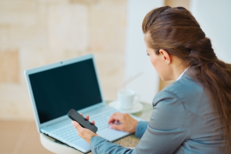 topicality: Business woman working with laptop on terrace. rear view