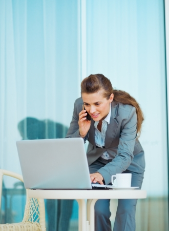 Business woman working with laptop and talking mobile phone on terrace Stock Photo - 20310013