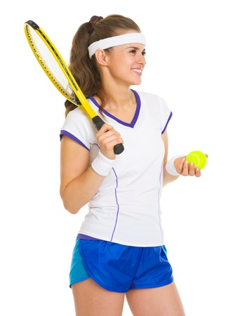 Smiling female tennis player with racket and ball looking on copy space photo