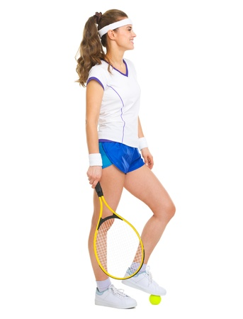 Happy female tennis player with racket and ball looking on copy space photo