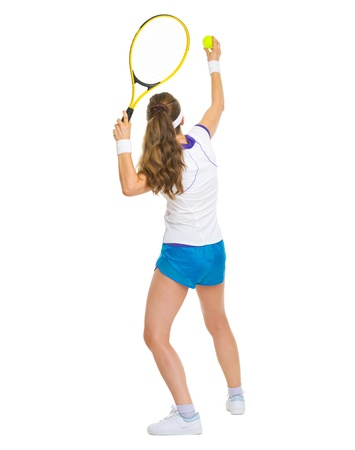 Female tennis player serving ball. rear view photo