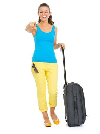 Smiling young tourist woman with wheel bag pointing in camera Stock Photo - 20356466