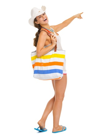Full length portrait of smiling young woman with beach bag pointing on copy space photo