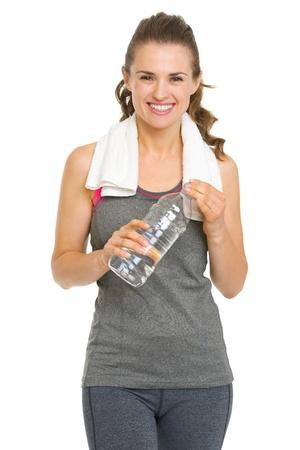 フィットネス タオルと水のボトルを持つ若い女性を笑顔