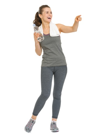 Full length portrait of smiling fitness young woman with bottle of water pointing on copy space photo