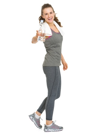 Full length portrait of happy fitness young woman giving bottle of water photo