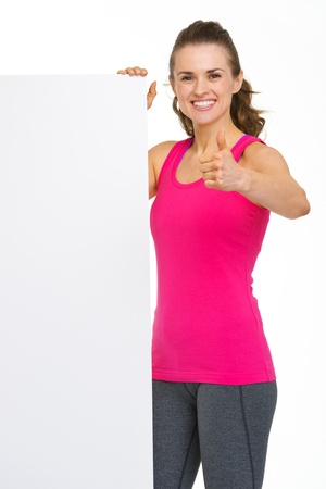 Smiling fitness young woman showing blank billboard and thumbs up Stock Photo - 20333365