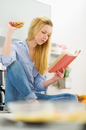 classbook: Young woman studying in kitchen