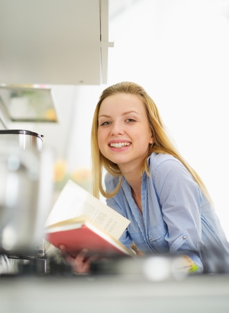 classbook: Happy young woman with book in kitchen