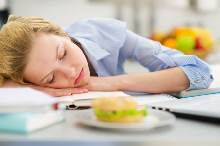 classbook: Teenage girl fall asleep while studying in kitchen Stock Photo