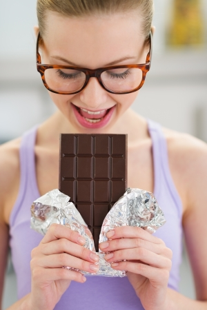 Teenage girl eating chocolate bar photo