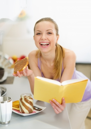 classbook: Happy teenage girl eating toast with chocolate cream while reading book