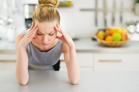 youthfulness: Portrait of stressed young housewife in modern kitchen Stock Photo