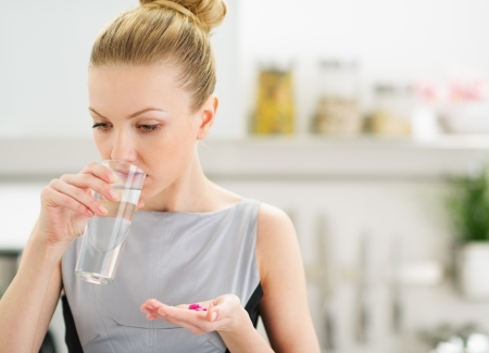Young housewife eating pills and drinking water Stock Photo - 20412477
