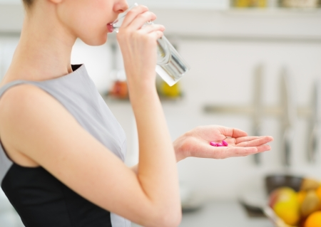 antibiotic pills: Closeup on young housewife eating pills and drinking water Stock Photo