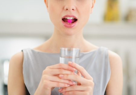 Closeup on young woman with pill in mouth Stock Photo - 20412497