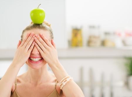 eyes closing: Adolescente feliz con la manzana en la cabeza de cierre los ojos con las manos