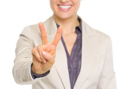 Closeup on smiling business woman showing victory gesture photo