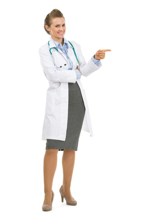Full length portrait of happy doctor woman pointing on copy space Stock Photo - 20467211