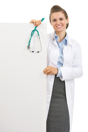 Happy doctor woman with stethoscope showing blank billboard photo
