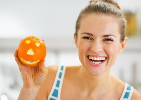 Smiling young woman showing orange with funny face photo