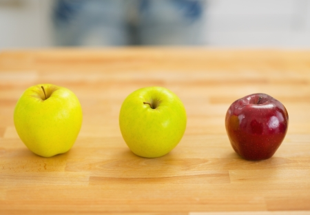 Two green and one red apple on cutting board Stock Photo - 20545304