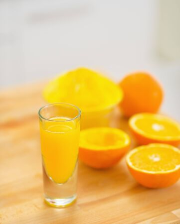 Closeup on glass of orange juice and oranges on cutting board photo