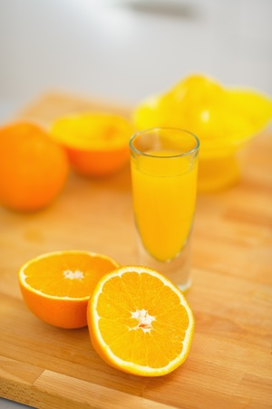 Closeup on glass of orange juice and oranges on cutting board Stock Photo - 20545305