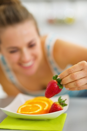 Closeup on happy young woman decorating plate with fruits photo