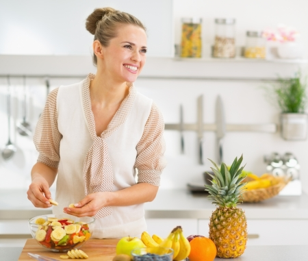 Happy young housewife making fruits salad photo
