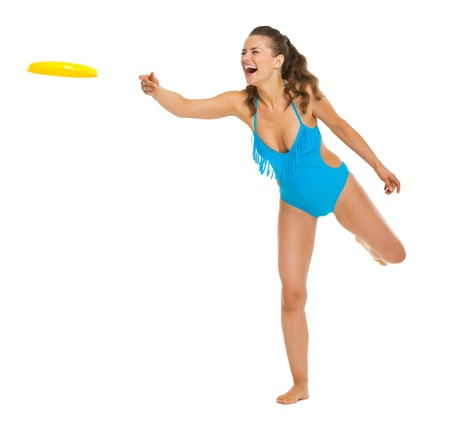 Happy young woman in swimsuit throwing flying disc Stock Photo - 20542777