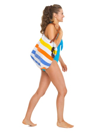 Young woman in swimsuit with beach bag going sideways Stock Photo - 20542797