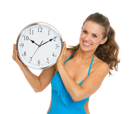 Happy young woman in swimsuit showing clock Stock Photo - 20542745