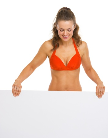 Happy young woman in swimsuit looking on blank billboard Stock Photo - 20542743