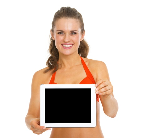 Smiling young woman in swimsuit showing tablet pc blank screen Stock Photo - 20542796