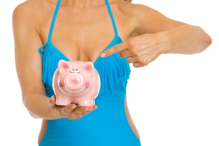 Closeup on woman in swimsuit pointing on piggy bank Stock Photo - 20542661